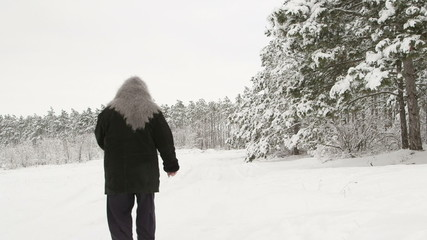 Elderly woman walking on snowy road through a forest in winter