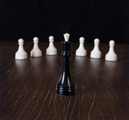 The Chess black queen in focus with white pawns.