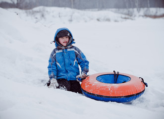 the boy sits in the snow , holding the tubing
