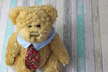 Office teddy bear in shirt and tie on rustic background