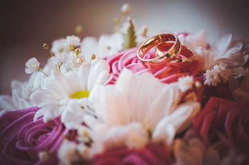wedding rings on top of bouquet