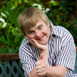 Cute boy with down syndrome doing thumbs up in garden. - 76062136