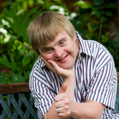 Cute boy with down syndrome doing thumbs up in garden.