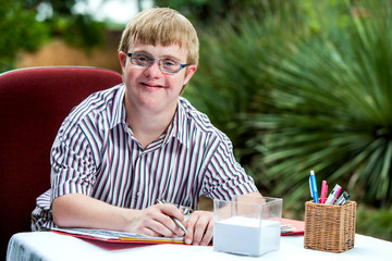 Handicapped boy at desk in garden.