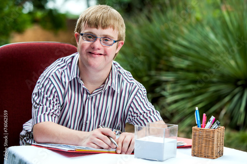 Leinwandbild Motiv Handicapped boy at desk in garden.