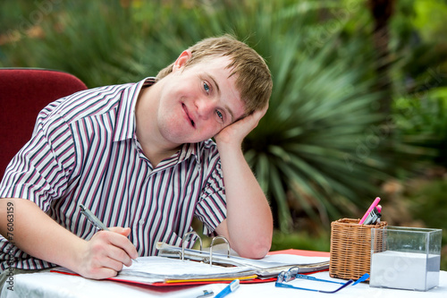 Handicapped boy resting on hand at desk. - 76063159