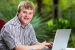 Handicapped young man typing on laptop in garden. - 76063575