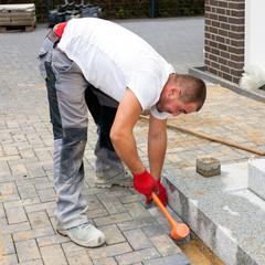 A worker creates a terrace of concrete paving stones.