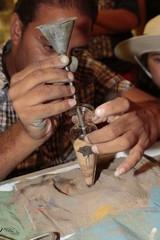 Hombre haciendo dibujos con arena en un bote de cristal.