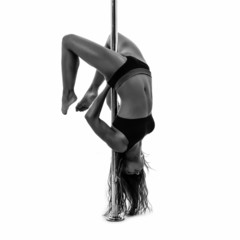 Silouette of woman performing pole dance. Studio shot, black and
