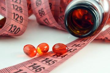 Measuring tape and bottle with pills. Dieting concept