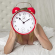 Woman holding alarm clock infront of face