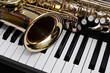 Leinwandbild Motiv Fragment of the saxophone lying on the piano keys