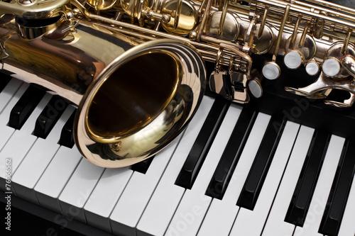 Papiers peints Magasin de musique Fragment of the saxophone lying on the piano keys