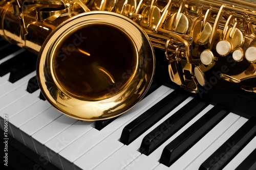Fragment of the saxophone lying on the piano keys - 76066577