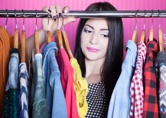 Young attractive disappointed woman searching for clothing