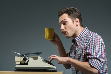 Author drinking coffee at typewriter