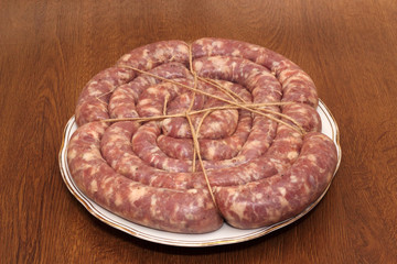 Ring of tied sausage on the white plate