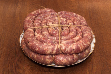 Two rings of tyied sausage on the white plate