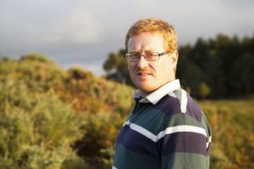 Hombre pelirrojo con gafas en el campo