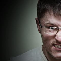 Portrait of powerful man in glasses showing teeth