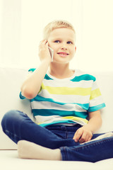 smiling little boy with smartphone at home