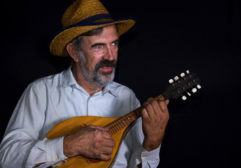 Portrait (low key) of an old country man with mandolin