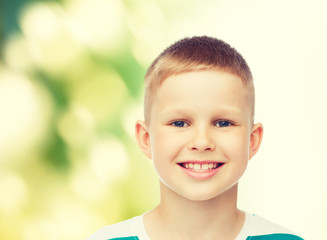 smiling little boy over green background