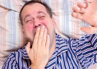 sleepy man yawning in bed