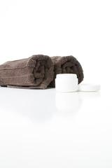 Offene Cremedose und Handtücher