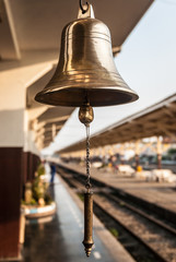 Closeup of a brassy bell at Thailand's train station.