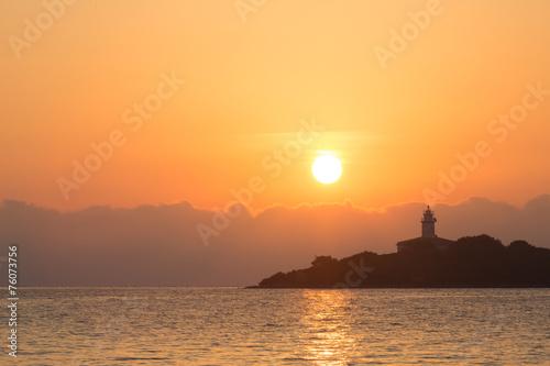 Leinwanddruck Bild Light house in Alcanada on the island majorca in the sunrise