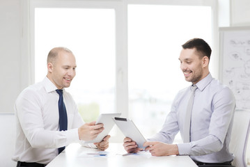 two smiling businessmen with tablet pc in office
