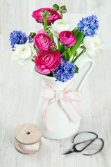 ranunculus and hyacinth flowers in a pitcher