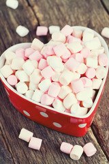 marshmallows in heart shape bowl on a wooden table