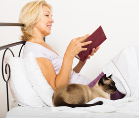 female pensioner with cat reading book