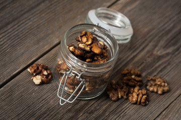 Walnuts in glass jar on wooden background