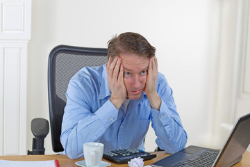 Mature man looking lost while at work