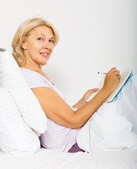Blonde mature woman  writing in diary