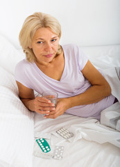 Mature woman laying in bed with pills and glass