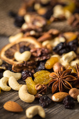 Close-up of nuts and dried fruits mix on wooden surface.