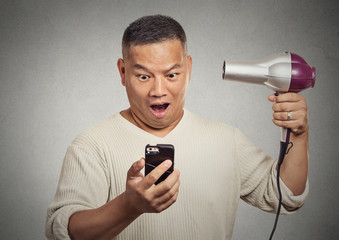 shocked surprised man looking on smartphone holding hairdryer