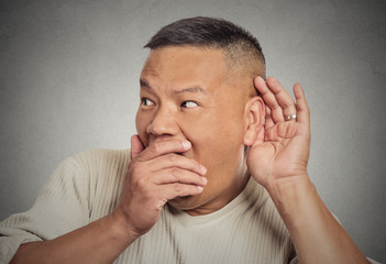 Shocked man hand to ear listening eavesdropping grey background