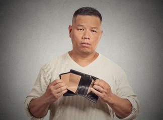 Sad man holding empty wallet isolated on grey background