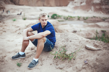 Young man sitting on the sand alone