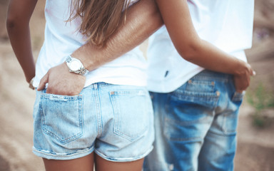 Couple holding hands in each other pocket