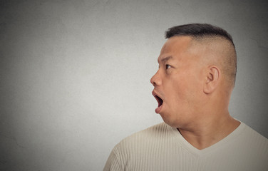 Side profile middle aged man speaking grey background