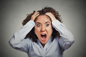 frustrated shocked business woman pulling hair out yelling