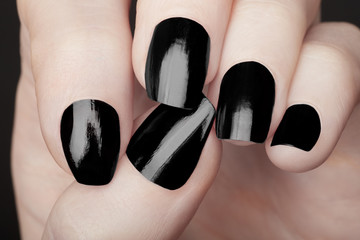 Black nail polish manicure on female hands
