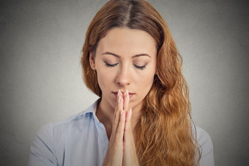 Portrait peaceful woman praying isolated grey wall background